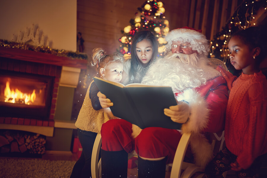santa reads to children from a book