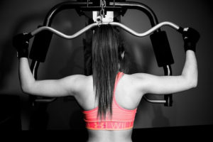 back of woman in pink bra lifting weights