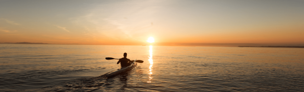 person kayaks at sunset