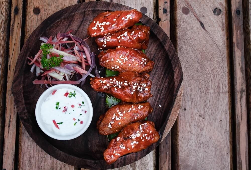 chicken wings on wooden plate with white dip and onions
