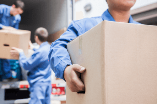 movers unload cardboard boxes from a truck
