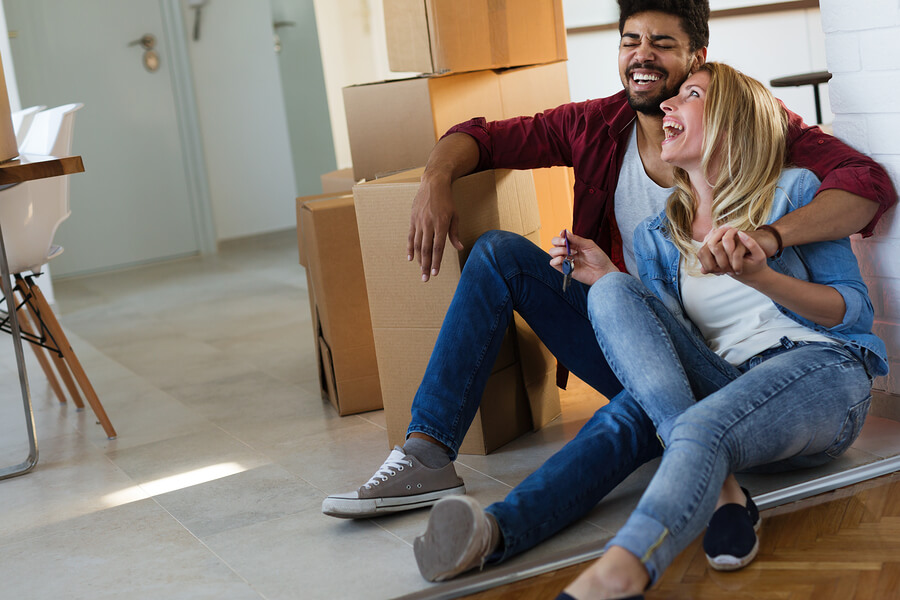 couple sitting on floor laughing next to cardboardboxes