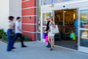 man and woman walk out of store in Millenia