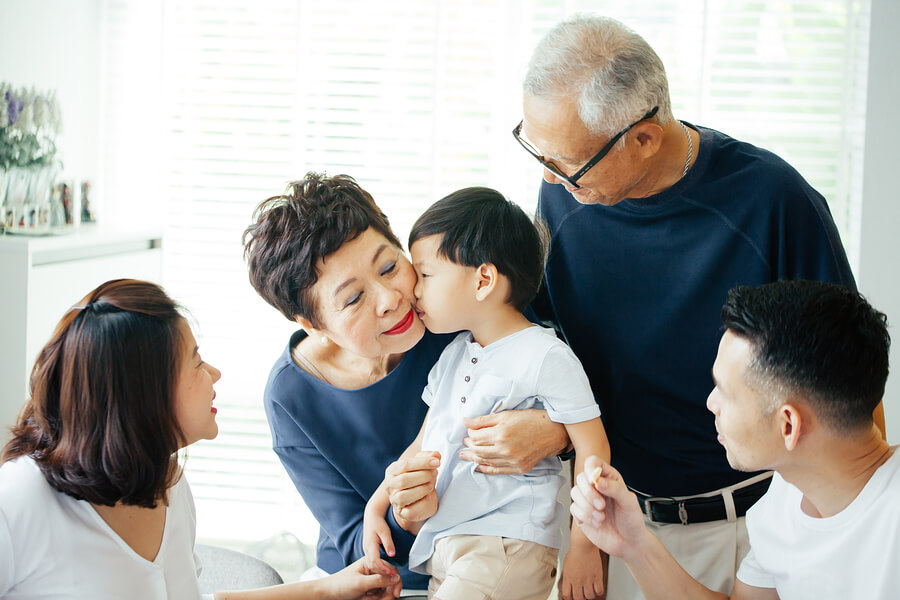 asian little boy kisses woman on cheek surrounded by family