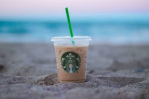 starbucks iced coffee in sand on beach