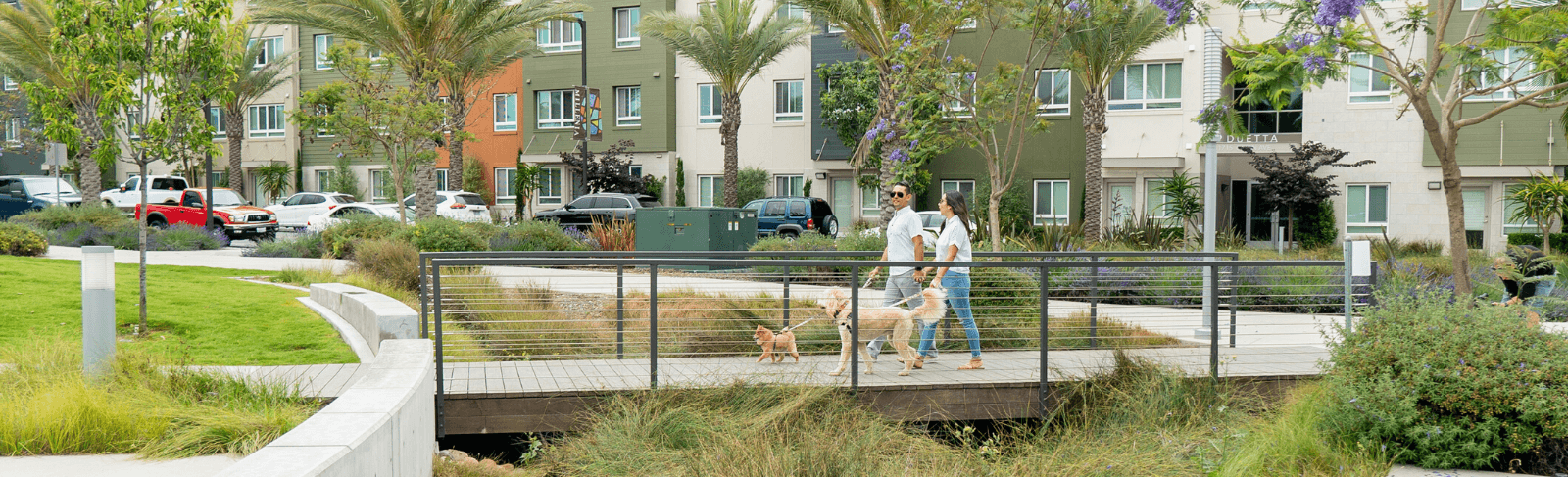 couple with dog walk over bridge at Millenia in Chula Vista