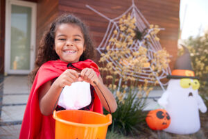 girl in cape holds orange bucket in front of halloween decorations