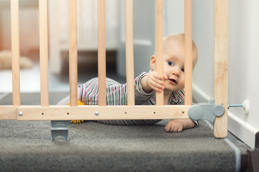baby lays at top of step holding baby gate