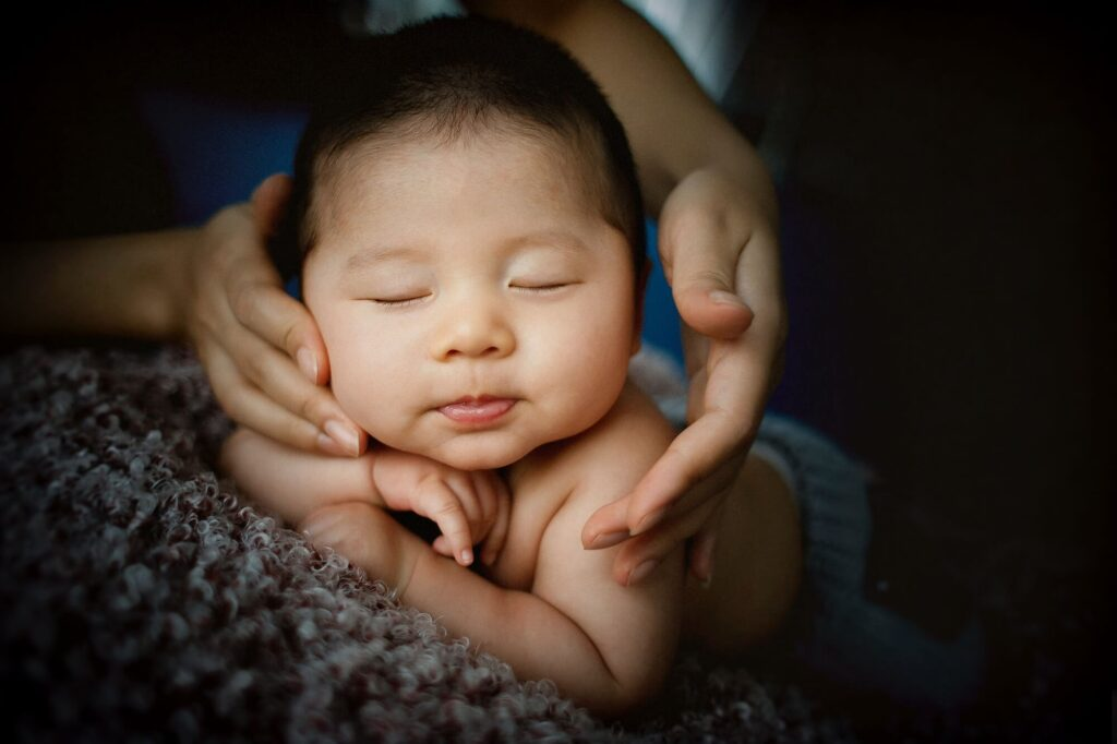 sleeping baby's face is framed by adult hands